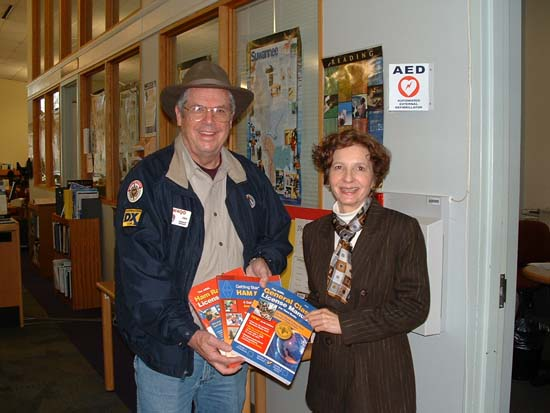 Jim, W4QO presents ham radio books contributed by NFARL to Lu Conti of the Roswell Library